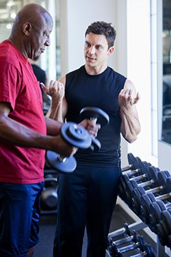 Image of senior man and fitness instruction near a weight rack at the gym