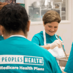 Peoples Health employee smiles while volunteering at Second Harvest Food Bank