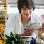 Woman with coupons at grocery store