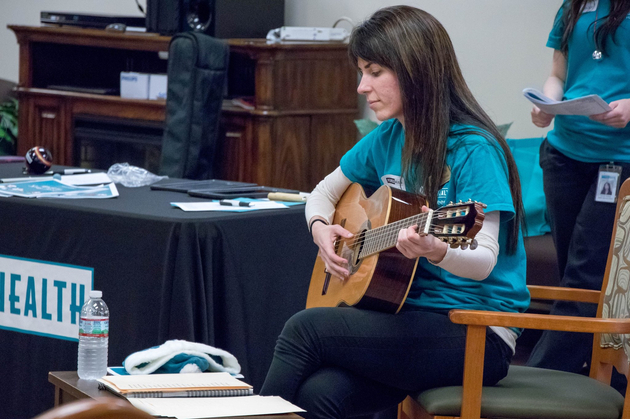 Peoples Health employee playing the guitar at a Christmas event honoring seniors