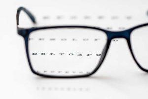 Closeup image of eyeglasses sitting on an eye exam chart
