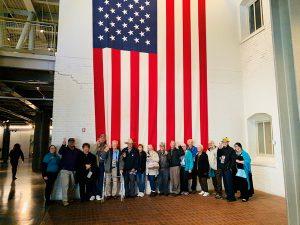 Seniors standing in front of flag