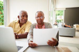 Shot of a african senior couple reading document with laptop at home